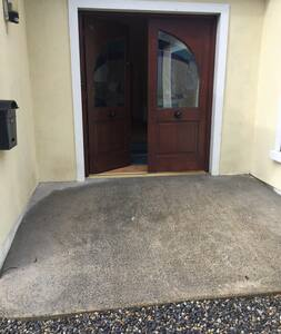 Ramp to door. House is all on one level throughout. Pebbled driveway but visitors can drive right up to the ramp shown in the picture.