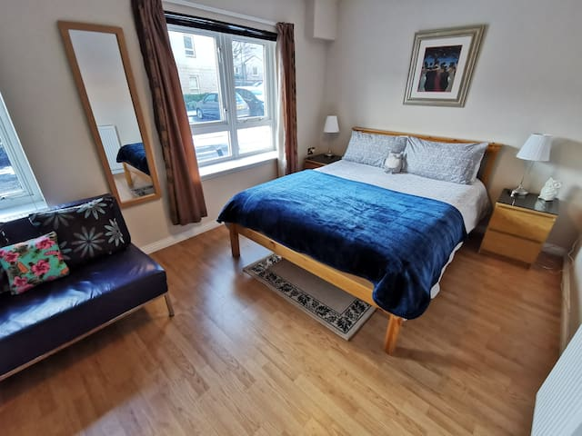 Spacious double bedroom 2, with double bed, bedside cabinets, sofa and wardrobes