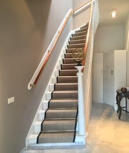 Via de entree kom je in een ruime hal met een brede trap naar boven. Bovenaan de trap kom je in een kleinere hal met aan de rechterkant de deur naar de kamer.