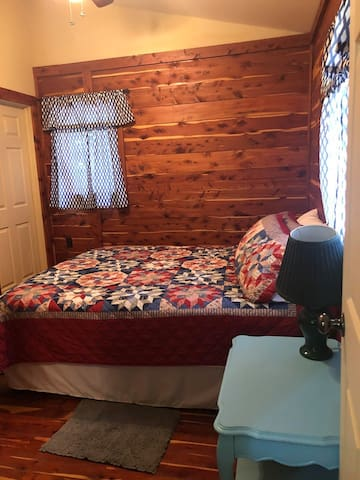 Bedroom with Queen size bed and night stand.