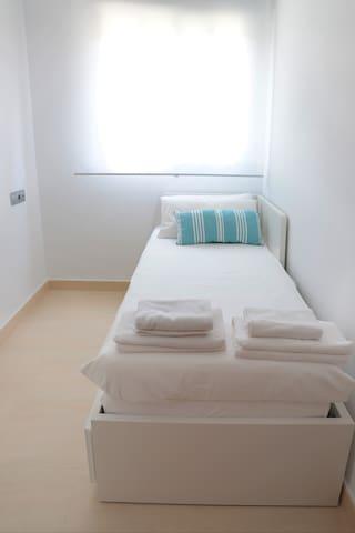 Tercera habitación con cama individual que se convierte en cama doble, con cajones amplios y armario pequeño.
