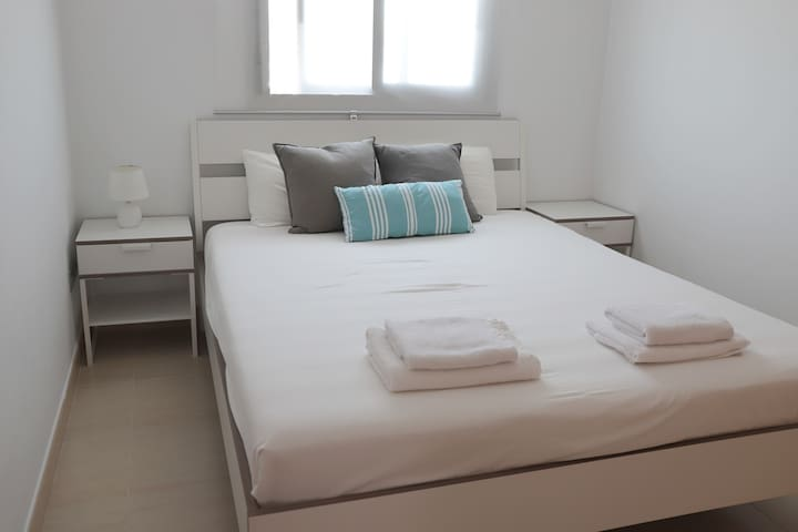 Segunda habitación con cama doble y armario, vistas a la montaña.