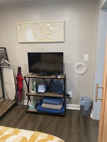 Bedroom with Smart TV, DVD player, hanging clothes rack and ironing board and iron. Yes, there are even 2 golf umbrellas for those unexpected spring showers!
