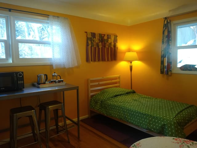 2nd guestroom has fridge, microwave, coffee maker, little table with stools, and a twin bed.