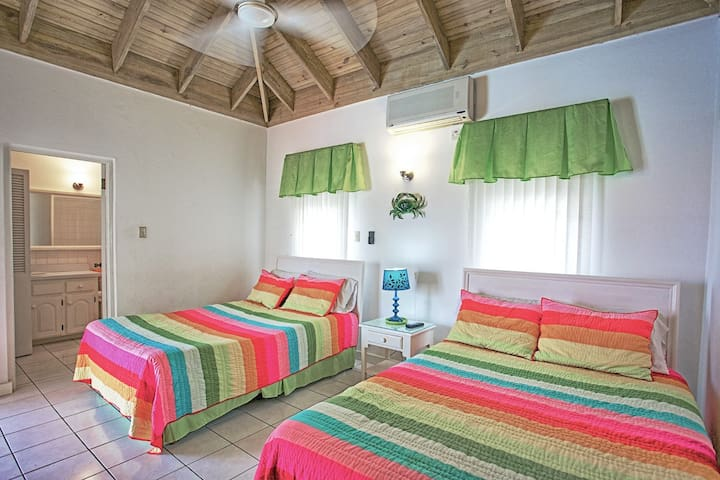 The second bedroom. Double beds; air-conditioned; ceiling fan; dressing table with mirror; 1 side table; 1 bedside lamp; bathroom en suite with tub and shower. All windows are screened.