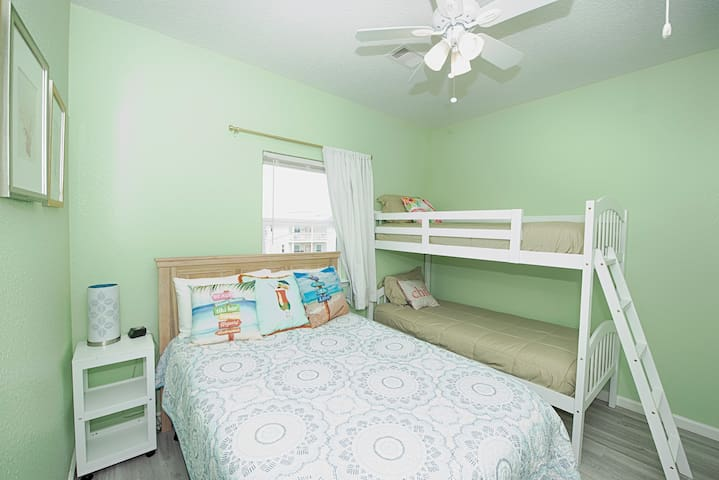 The guest bedroom includes a full bed and set of bunk beds