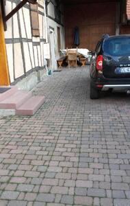 L'entrée se situe au fond de la cour, à gauche, juste avant la table et bancs en bois