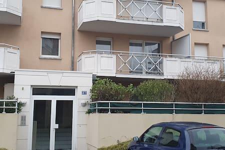 Une large porte d'entrée. Le logement est celui juste en haut à droite au premier étage.  Vous voyez sa grande terrasse.  Il y a des escaliers derrière la porte  d'entrée.