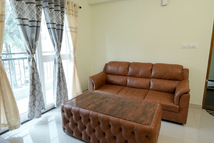Living Room with Balcony for Fresh air and day light, comfortable sofa and table to sit and enjoy movies or music on Smart TV connected to WiFi network.