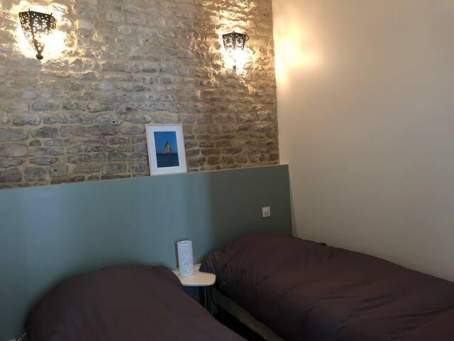 La chambre avec les 2 lits simples. La literie est très confortable. Elle dispose également de rangements.