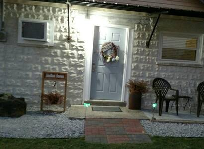 The entrance has pavers that slope up to the concrete stoop and there's about a four inch step up into the cottage. There's a security light as well as a porch light.