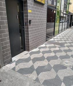 Calçada plana, sem degraus na porta de entrada do prédio.
