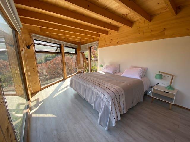Habitación Viento, cama SUPER King, cortinas en todas las ventanas con Black out y screen, silla mecedora de mimbre con vista a los cerros.