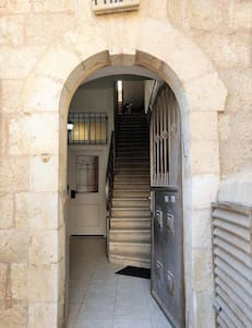 The white door is the entrance door of the apartment, without stairs.
