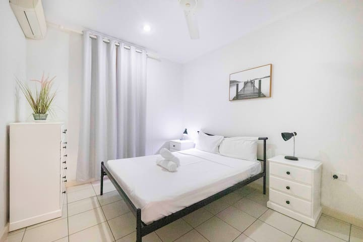 A contemporary bedroom is furnished with a queen bed dressed in high-quality linen and built-in, mirrored wardrobes and has air conditioning.