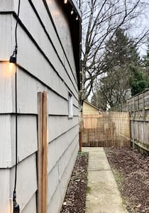 To the right side of the garage, your path will take you around to the Airbnb entrance and lock box.