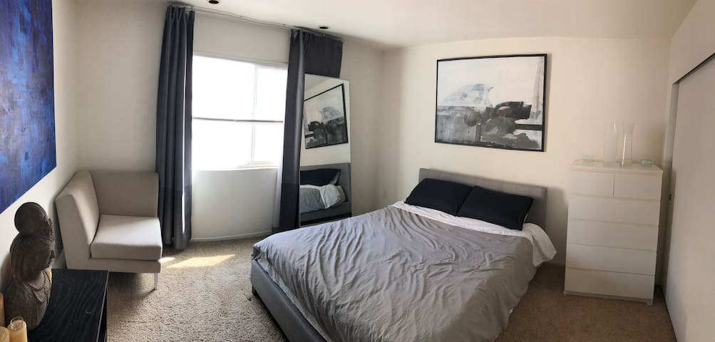 The 2nd room down the hallway is this master bedroom. 1 queen bed, luxury high thread-count sheets, cool & original hand-painted abstract art, window looking over the alley, white Ikea dresser, large beautiful blue painting, and shiva sculpture.