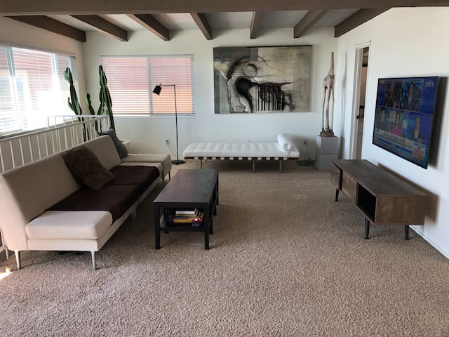 The 2nd level. A large open space w/designer furniture, decorated in a minimalist & modern style. More beautiful, one-of-a-kind art, large flat-panel, smart TV. Cool, large cactus, fig trees & succulents provide a natural indoor-outdoor vibe.