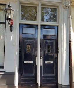 Vanaf het trottior kun je de voordeur bereiken. Bij de deur hangt een grote lamp. De ingang is smal en ook de gang is erg smal.