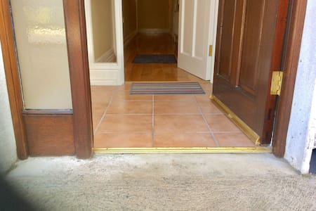 Front door entrance. No steps and a smooth concrete area gently sloping to doorway.