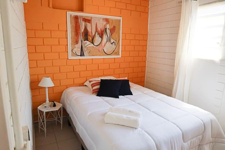 Quarto 2 - Cama Casal, mesas laterais, comoda + espelho. Ventilador de teto + ar condicionado.