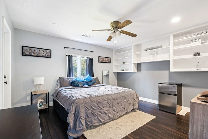 Private bedroom with King Size Bed, comfortable mattress, soft linens and an adjoining bathroom.   *Wall Mounted SmartTV *Mini-Fridge *Black Out Curtains *Ceiling Fan *Closet & Clothing Storage