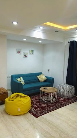 The living area has a sofa, 2 bean bags, centre table. Minimal decor, maximum comfort.