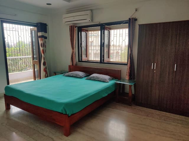 Bedroom1 - Spacious, well-ventilated with a king size bed along with 2 side table and large cupboard. The room comes with an attached bathroom and balcony. The windows has mosquito nets installed. It has AC as well.
