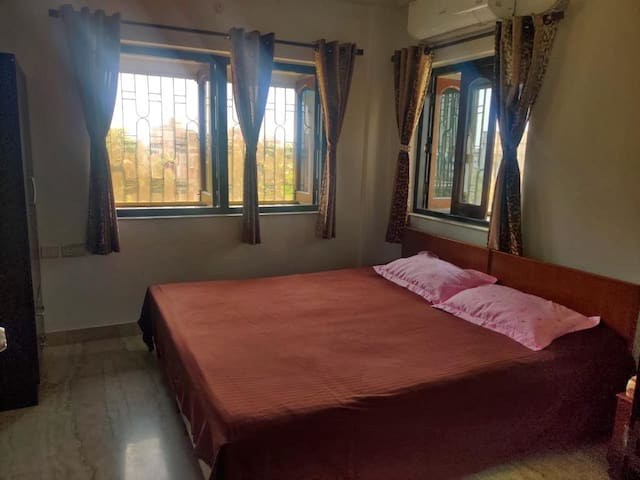 Bedroom2 - a king size bed, a cupboard, a side stool and AC. The room is very well ventilated.