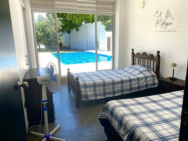 Habitación con tres camas sencillas y salida directa a la piscina / Room with three single beds and direct access to the pool