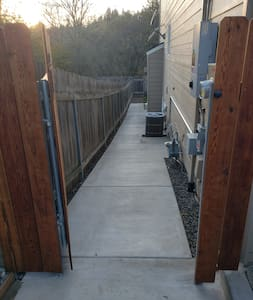 Wide entrance gate. One small step to landing in front of the gate.  Cement walkway slope is not excessively steep but is not ADA rated. Width will allow wheelchair passage.