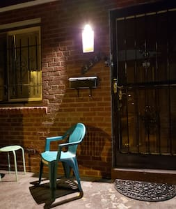 The front door with chairs and small tables on the porch. Digital code locks to the entrance.