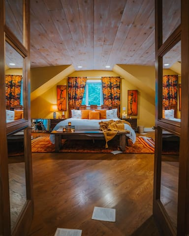 The extremely spacious Barn House Master has a king sized bed, chaise, love seat in front of the fireplace, as well as a desk under the window.