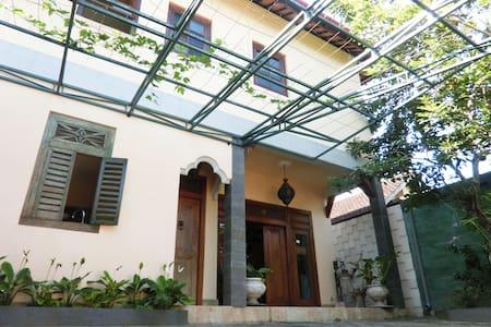 Front Porch, featuring antique Javanese window, Kitchen door and a wide main Entrance door