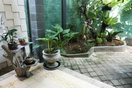 A flat paved parking leading to a step to the front porch, past a lush garden patch.
