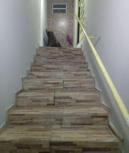 Entrada principal para a acomodação oferecida, possui luz com  sensor de presença, no início da escadaria