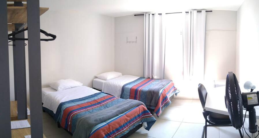 Confortável quarto com duas camas de solteiro, closet com cabides e prateleiras, frigobar, e um ventilador, para sua comodidade.