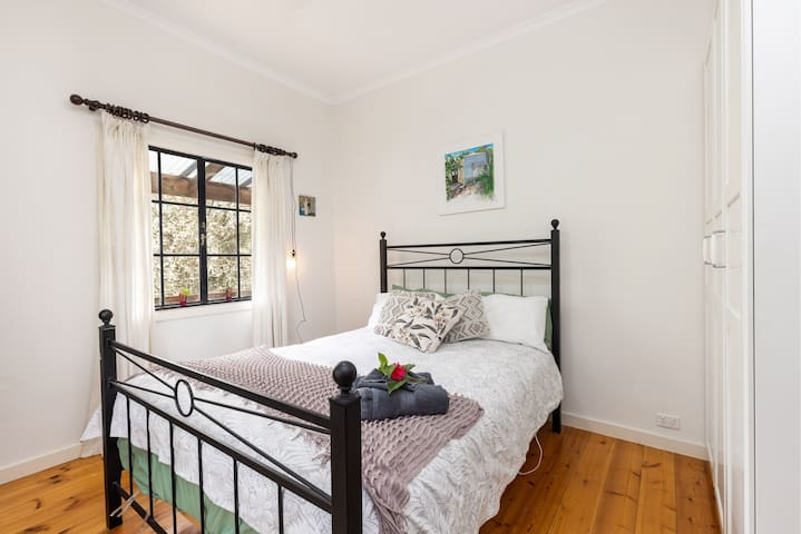 Main bedroom, with the view through the original iron colonial windows through to the blossom. Queen size bed. Simple in its furnishings, cosy and nurturing, and always with flowers awaiting you on check in.