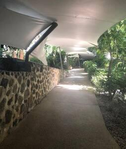 pasillo para acceder al elevador, albercas, mesas con asador y jardines.