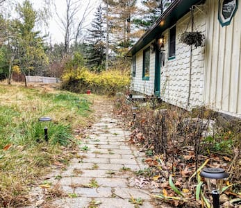 Walk from the drive to the left and you will see a brick path that leads to the door 50 feet along the path on the right. There you will see a green door with an electronic key pad.