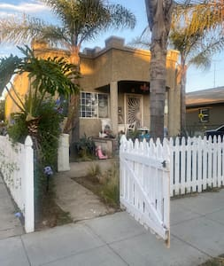 White picket fence has a wide person-sized gate and double wide driveway entrance that slides to the left.