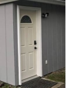 Motion detecting light, seen on the right side of the door, automatically comes on when you pull up in the driveway. (as long as it is dark outside).  One small curb on the concrete in front of the door. Keypad located on door.
