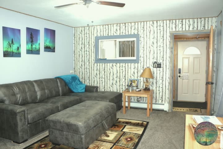 Bright, welcoming living-room has large couch, softly lit lamps or bright LED's with ceiling fan overhead, door to entryway.