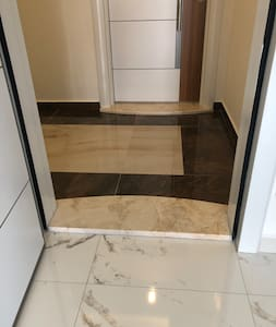 There is a door into an apartment. There is a small step