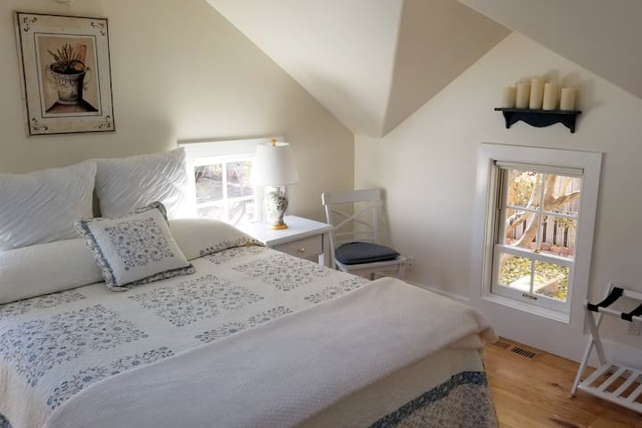 bedroom with very comfortable queen bed, offering 3 double hung window views of the grounds