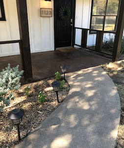 Smooth sidewalk, leading to front door from gravel driveway
