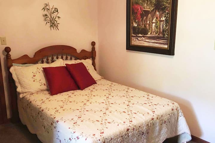 The hall bedroom is across from the hall bath. It has a double bed and dresser as well as a walk-in closet and ceiling fan.