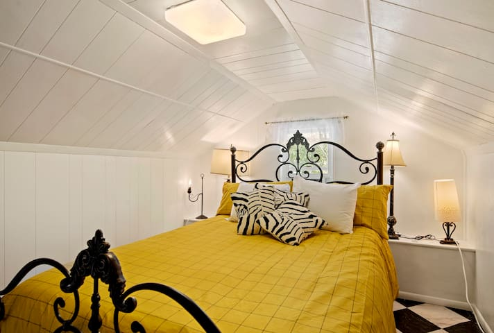 A finished attic bedroom with a queen bed, a/c and lots of quirkiness