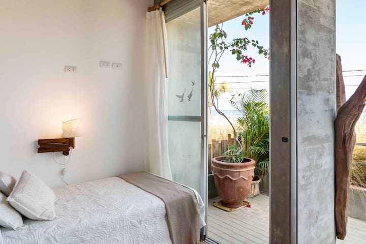 """Room #2. """"Venado"""" Two beds together or they can be separated depending on how you want to place them.  Large movable glass windows that let in light and fresh air."""