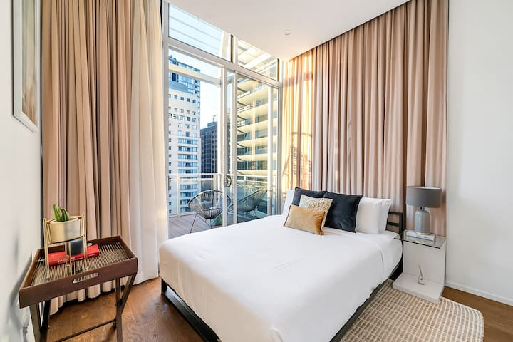 The bedroom opens to a private balcony with stunning views over the city. It features a queen bed topped with luxury hotel-style linens.